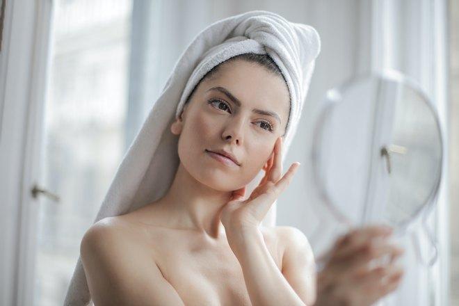 Девушка с полотенцем на голове смотрит на свое отражение