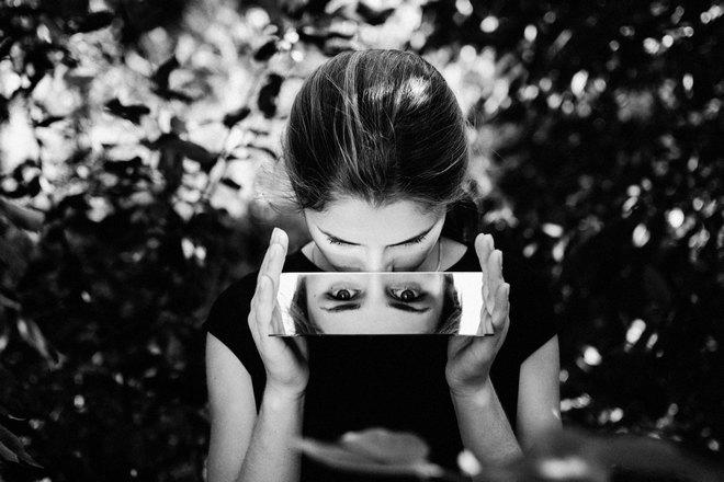 Девушка держит небольшое зеркало