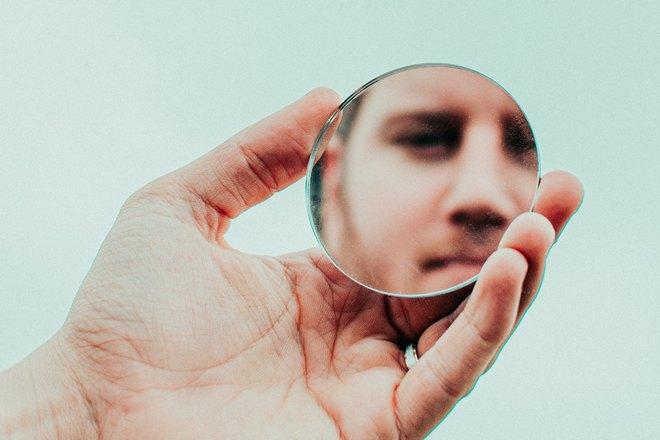Мужчина отражается в маленьком круглом зеркале