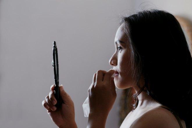 Девушка внимательно смотрит в небольшое зеркало