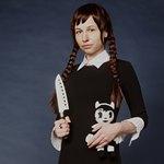 Девушка с косичками держит нож в правой руке
