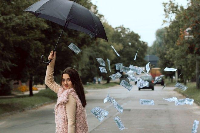 Девушка с зонтиком смотрит на летящие купюры