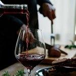 Красное вино наливают в большой бокал