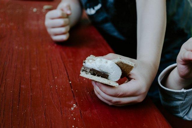 Бутерброд в руке над столом