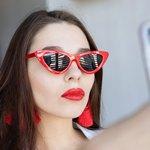 Девушка в очках с красными серьгами