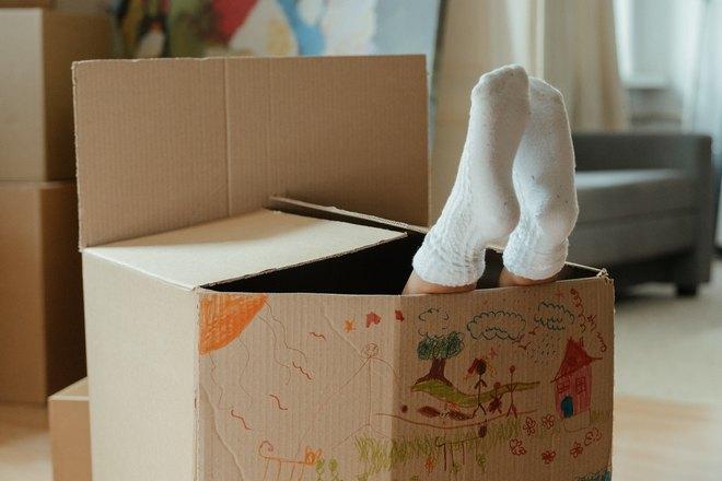 Ступни в носках торчат из картонной коробки