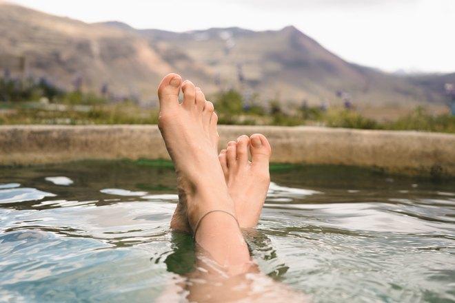 Ступни в воде не фоне гор