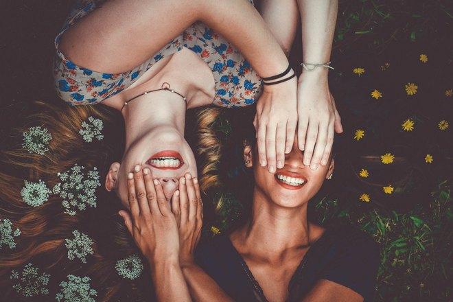 Улыбающиеся девушки прикрыли глаза ладонями