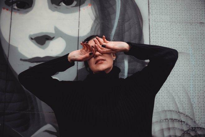 Девушка в черном закрыла глаза руками
