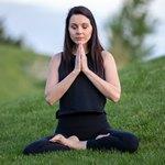 Женщина медитирует на траве