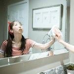 Девушка вытирает зеркало