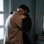 Плачущая девушка обнимает кого-то возле зеркала