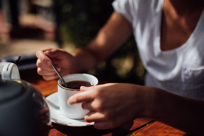Кто-то держит чашку чая с ложкой