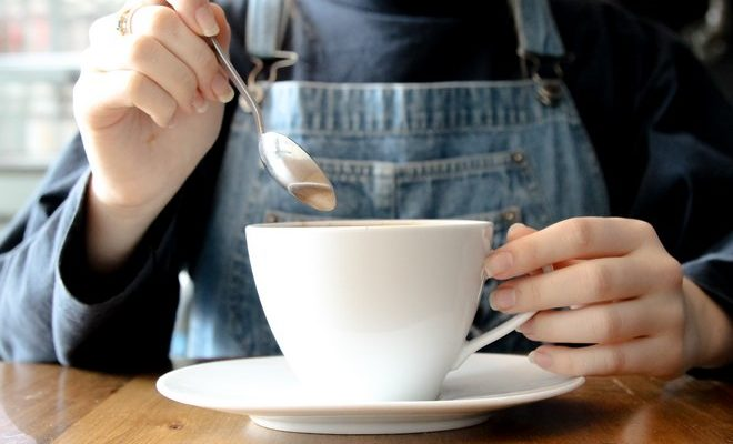 Девушка в джинсовом комбинезоне с чашкой чая
