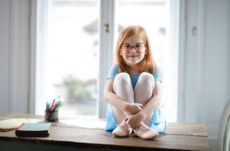 Девочка сидит на столе