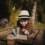 Мальчик читает книгу на столе