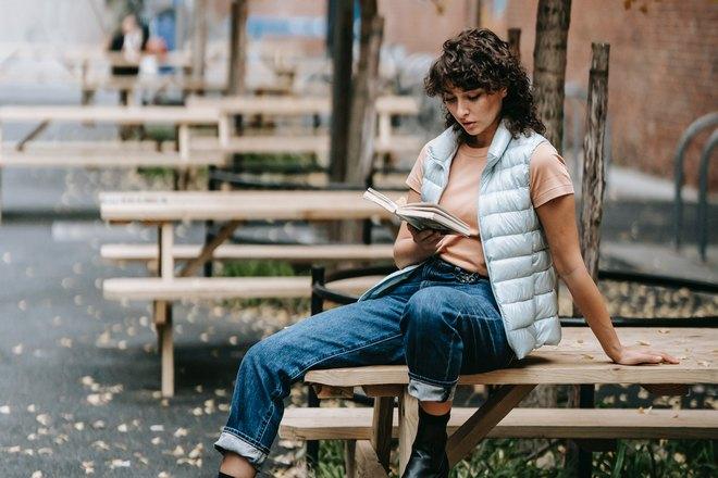 Девушка сидит на столе и читает