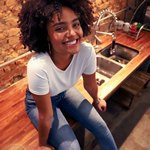 Девушка сидит на столе и улыбается