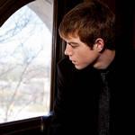 Парень смотрит из окна на похороны