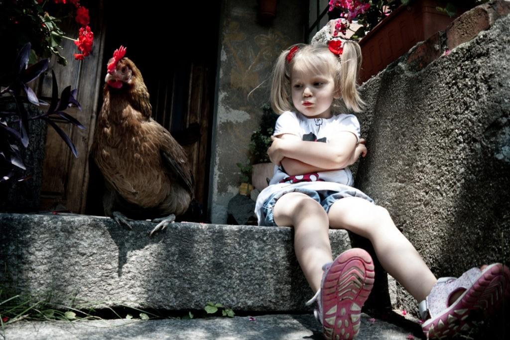 Девочка с курицей на ступеньках