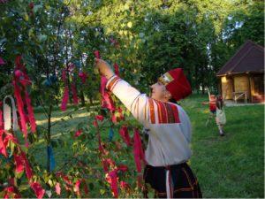 Девушка привязывает красную ленту на березу