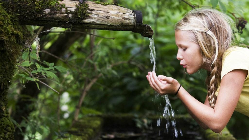 Девушка умывается родниковой водой