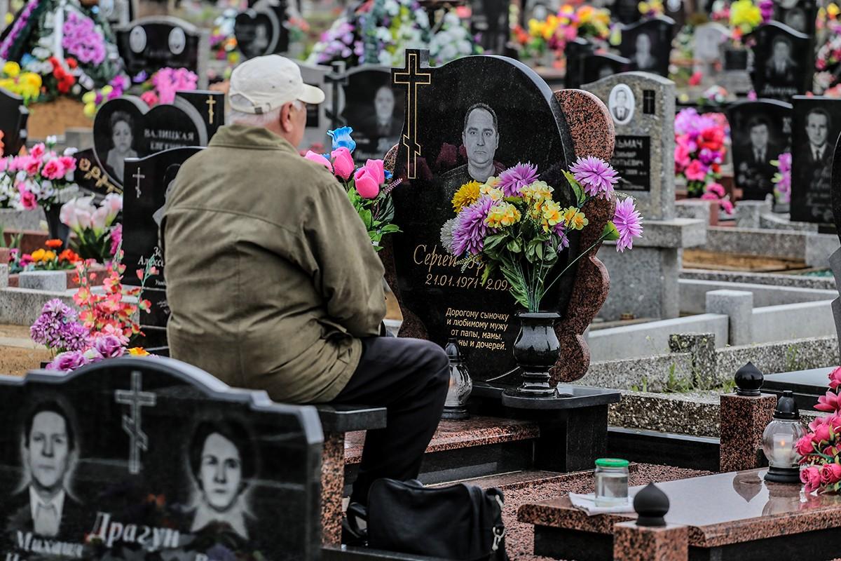 мужчина сидит возле памятника