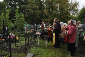 батюшка читает молитву на кладбище