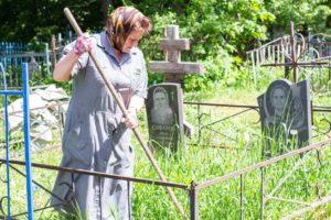 женщина косит траву на кладбище
