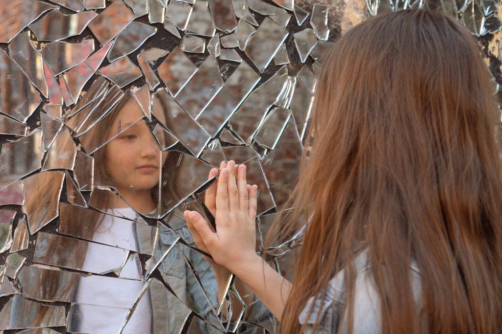 девочка на фоне стены из осколков зеркала