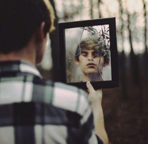 молодой человек держит в руках разбитое зеркало