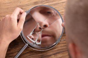 мужчина смотрит в разбитое зеркало