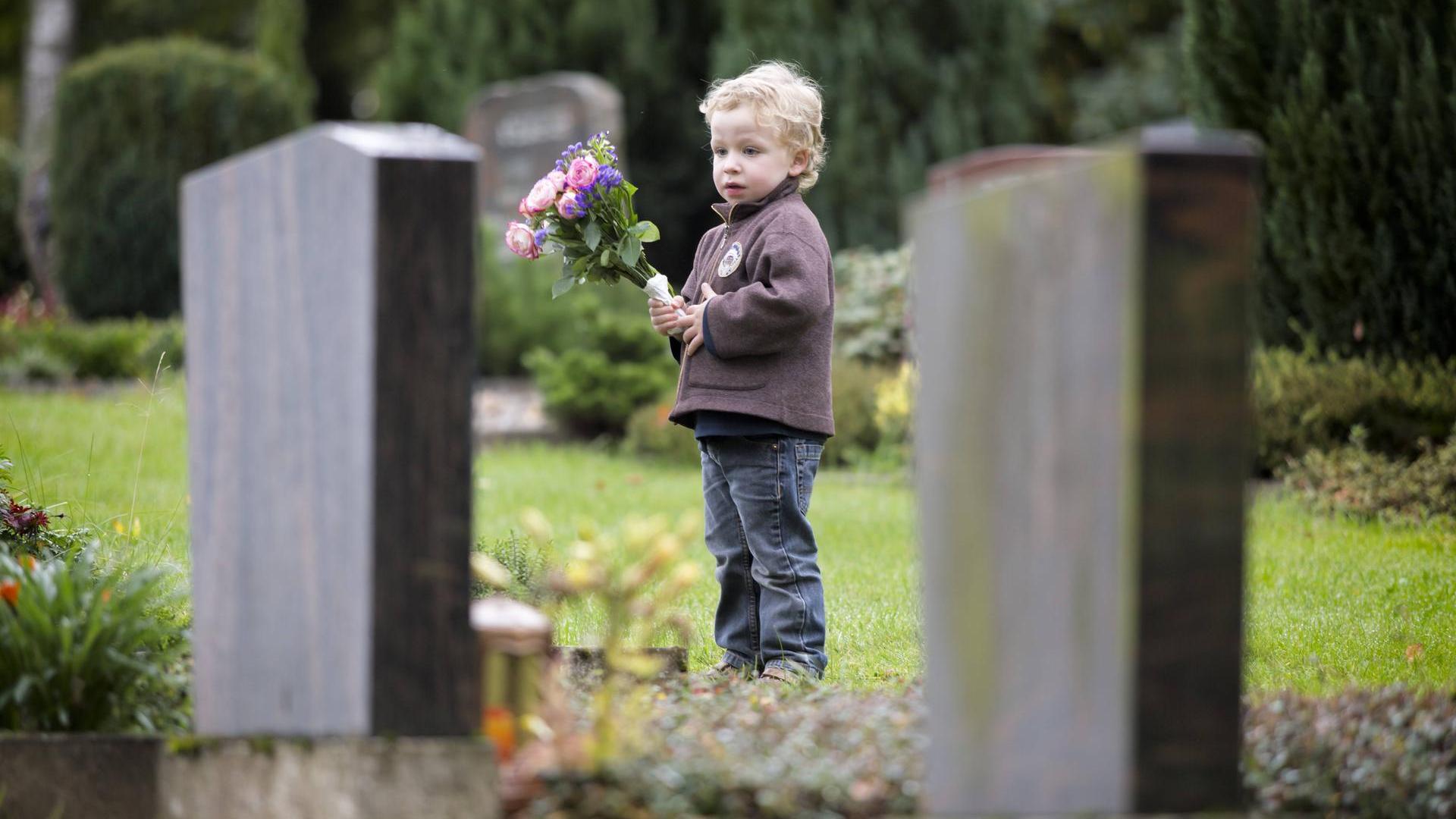 ребенок с цветами стоит на кладбище